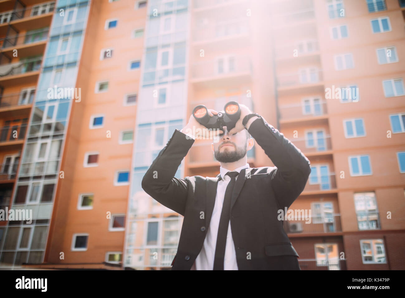 Handsome Businessman with binoculars spying on competitors - Stock Image