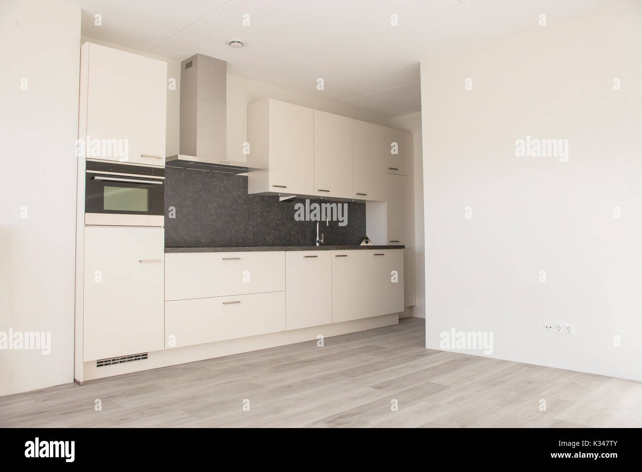 . Modern white kitchen in new empty house with wooden floor Stock