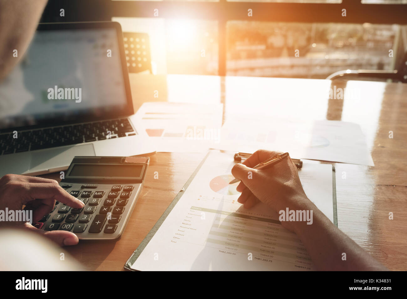 Close up Businessman using calculator and laptop for calaulating finance, tax, accounting, statistics and analytic research concept - Stock Image