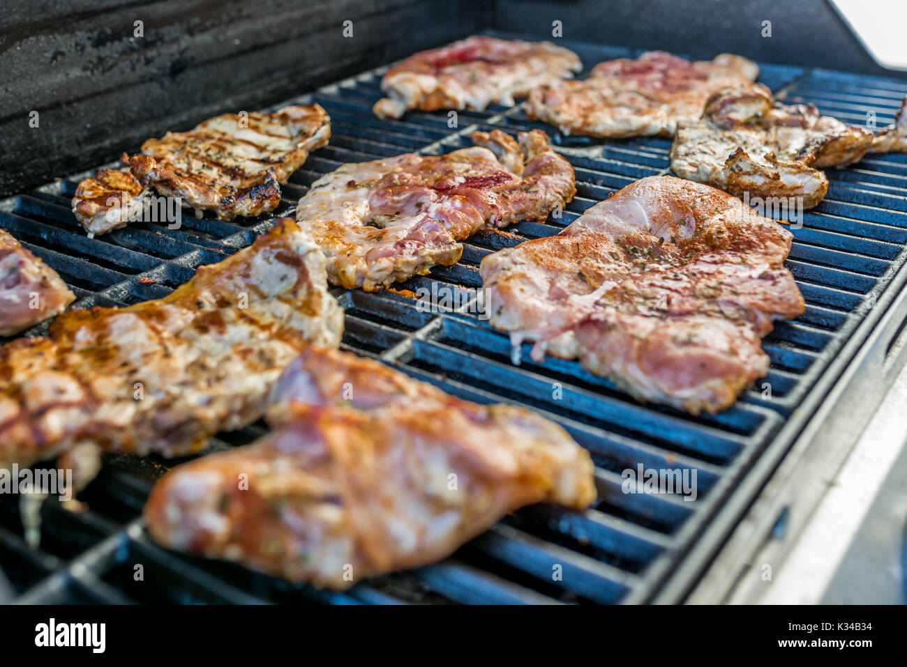 Delicious pork steaks with seasoning on the grill - Stock Image