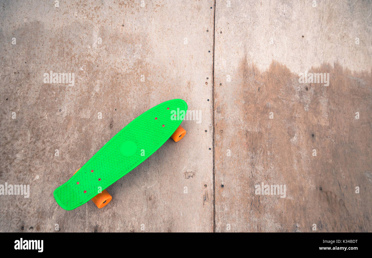 Single Green Penny Board On A Wooden Half Pipe Stock Photo