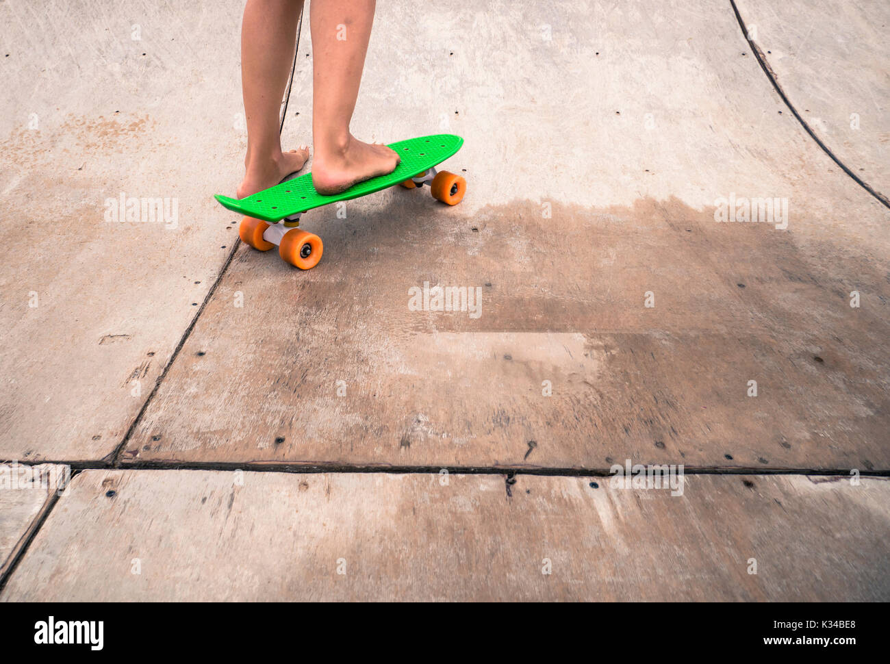 Woman Riding A Penny Board On A Wooden Half Pipe Stock Photo