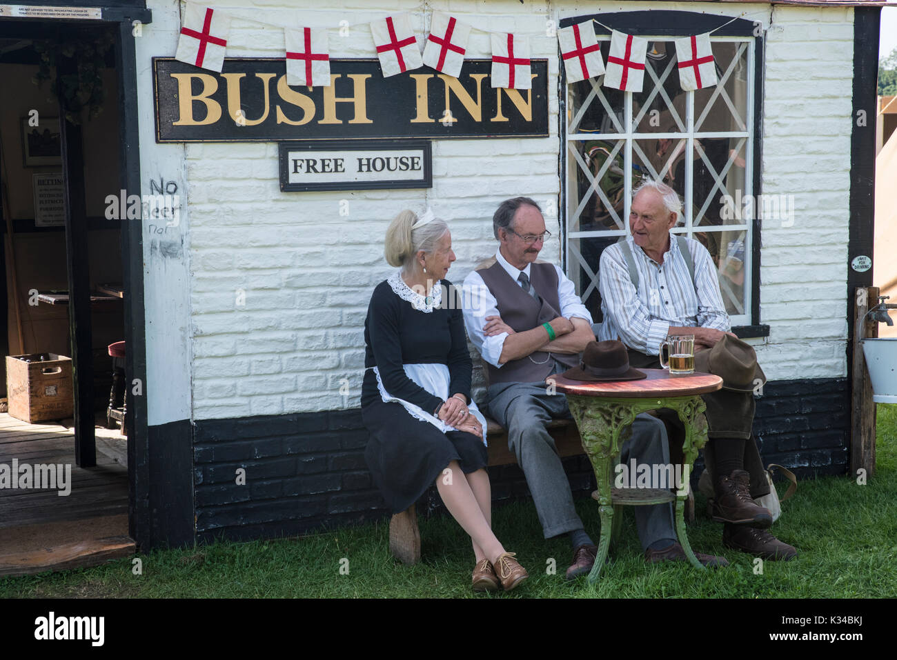 KENT, UK - AUGUST 28TH 2017: A model set of a traditional 1940s war-time public house with actors in costume sitting outside, at Military Odyssey, UK. - Stock Image