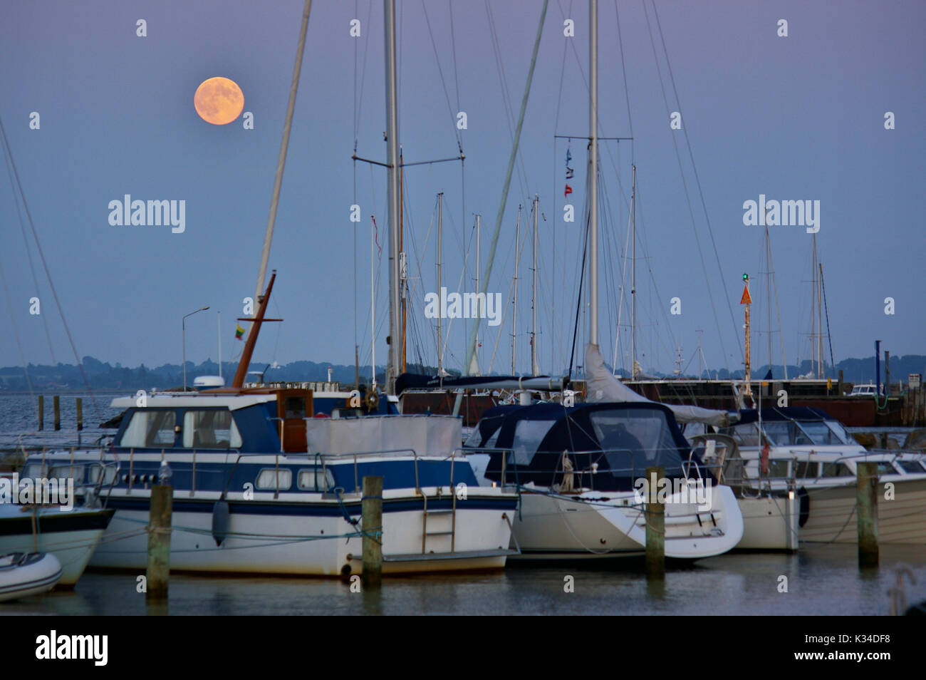 Yachts in a marina on the island of Ærø, Denmark at full moon - Stock Image