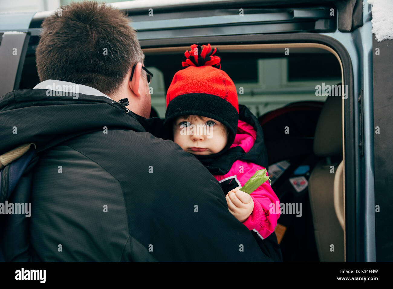 Dad carrying his daughter to the car during the winter. - Stock Image