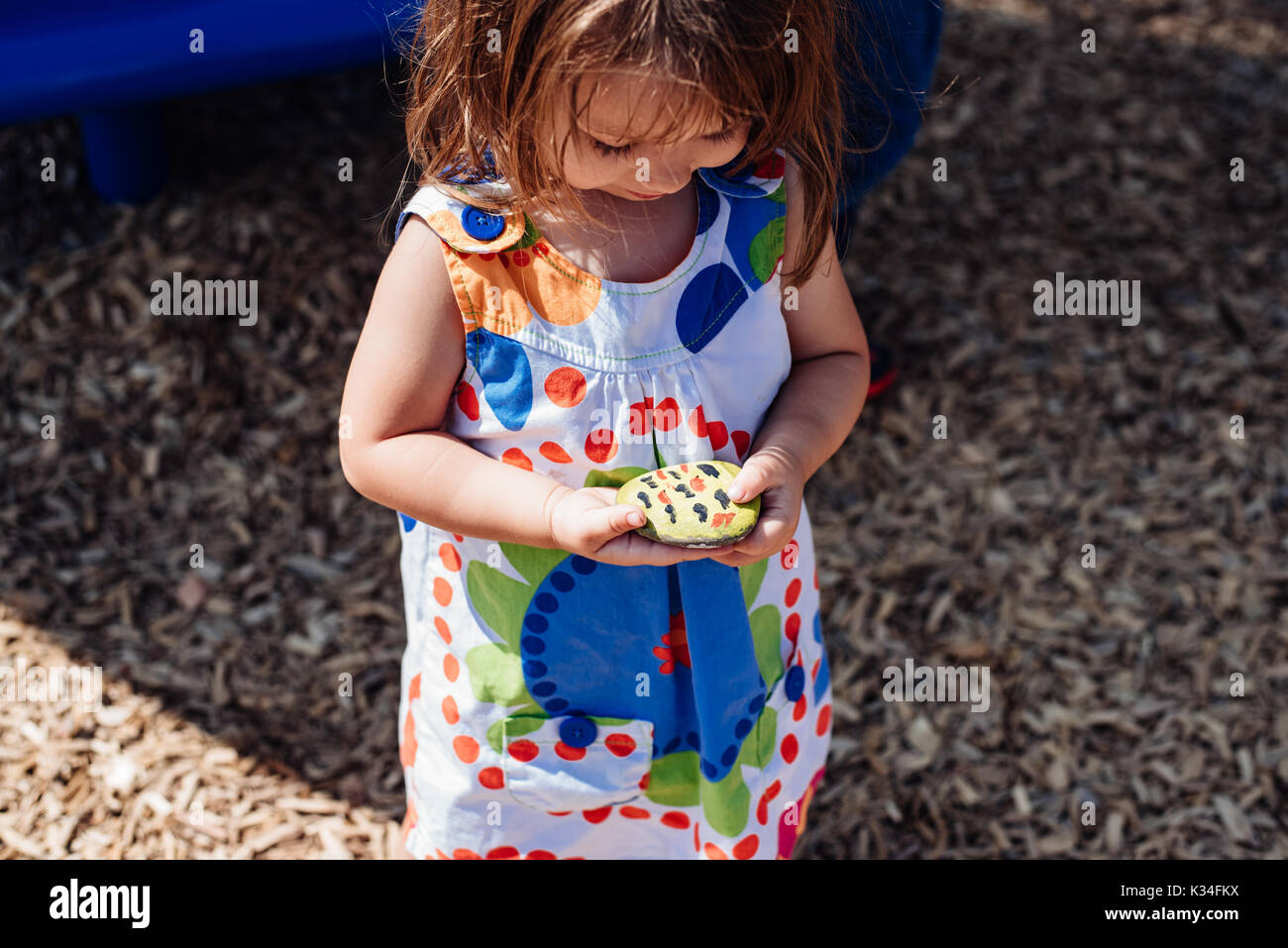 A little girl looking at a painted rock she is holding - Stock Image
