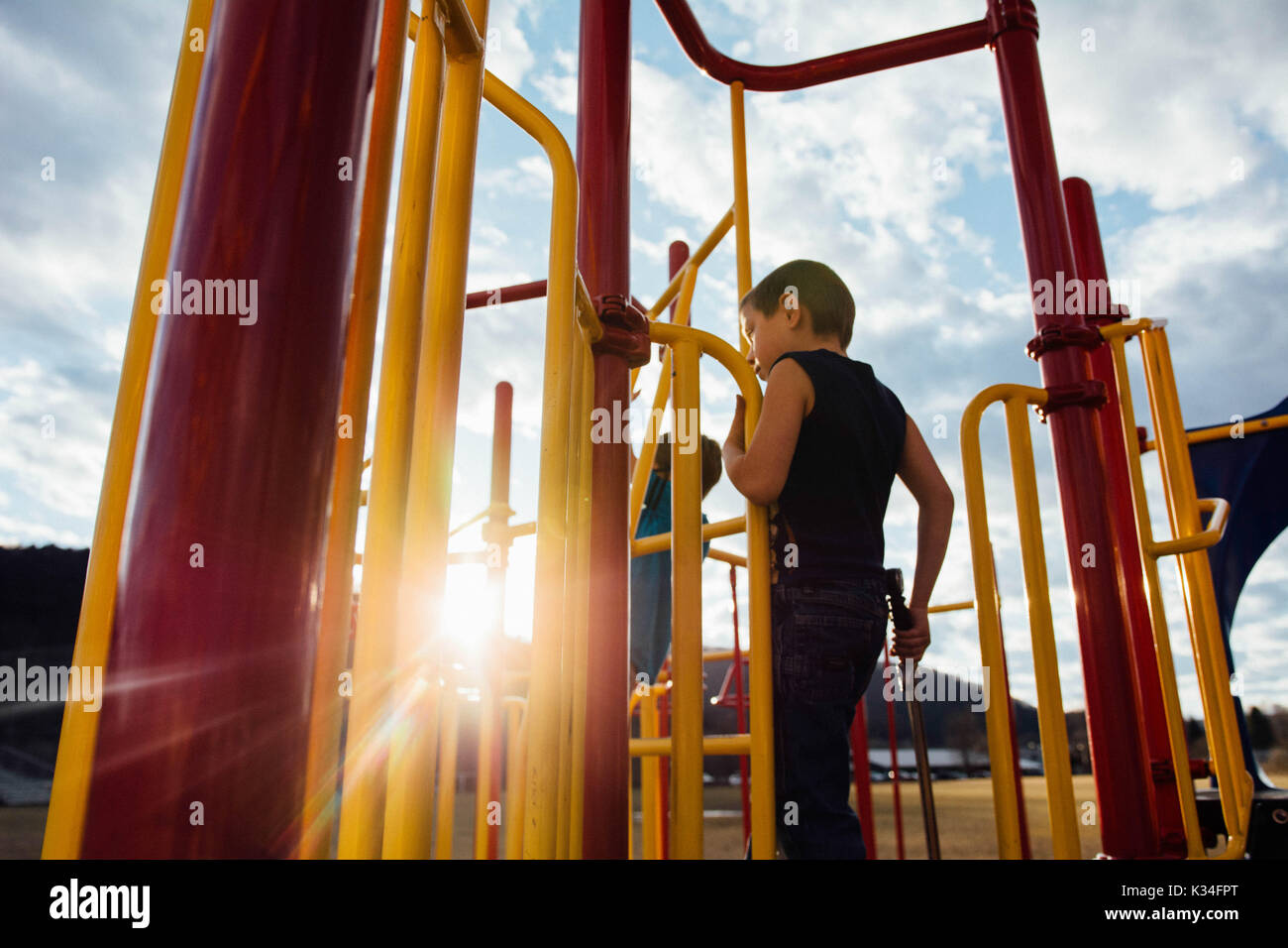 A boy plays on playground equipment at sunset. - Stock Image