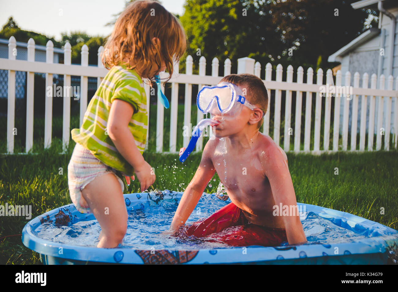 A boy wearing a scuba mask looks at a little girl in a kids swimming pool - Stock Image