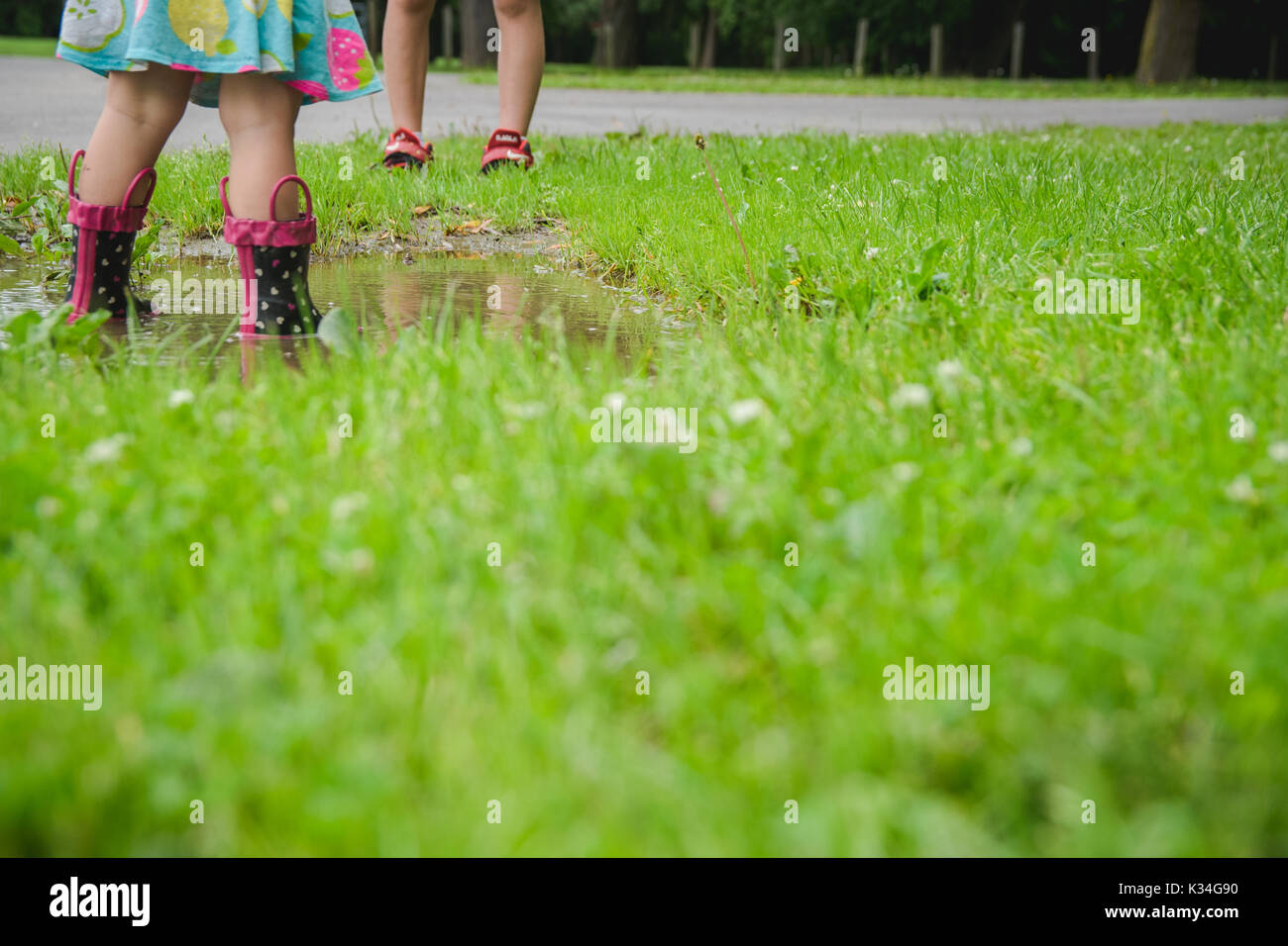 Children stand in a mud puddle wearing rain boots and with feet only pictured. - Stock Image