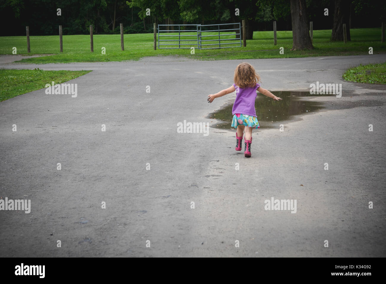 A toddler girl runs toward a mud puddle in a park. - Stock Image