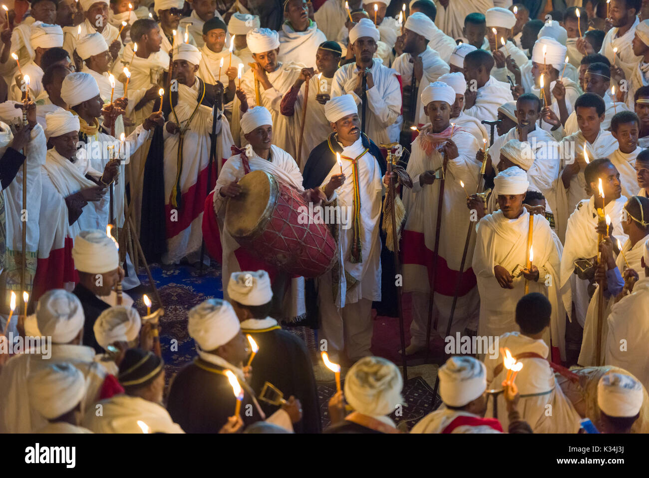 Priests chanting prayers by candlelight in the courtyard of Bet Medhane Alem church, during the prayers on Ethiopian Orthodox Easter Saturday, Lalibela, Ethiopia - Stock Image
