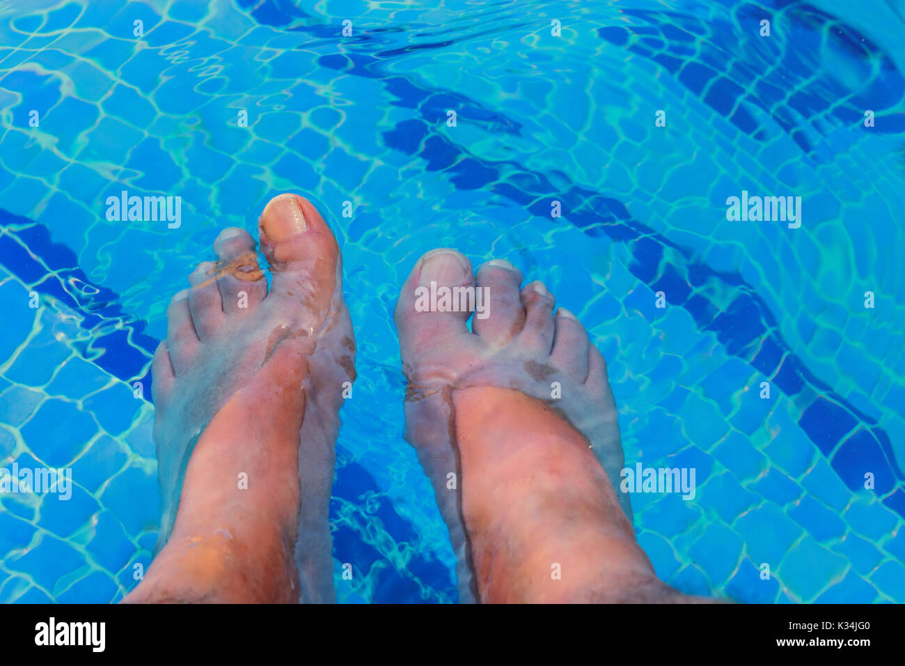 Men feet in a beautiful swimming pool with blue tiles. - Stock Image