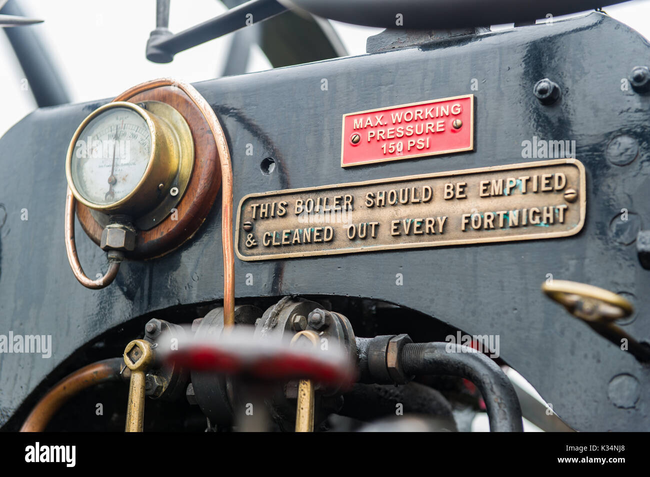 Steam engine pressure gauge, pipes and warning sign. - Stock Image