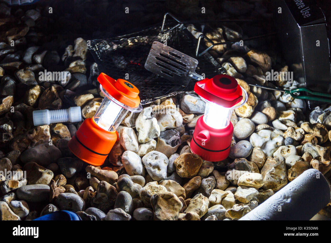 Close-up of two red camping lanterns illuminating a stony beach at night, after a barbecue - Stock Image