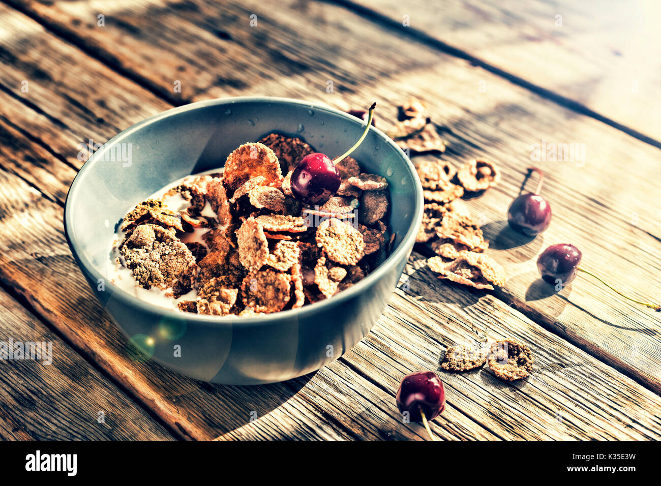 Healthy breakfast. Flakes with milk and fresh cherries, on a wooden table. - Stock Image