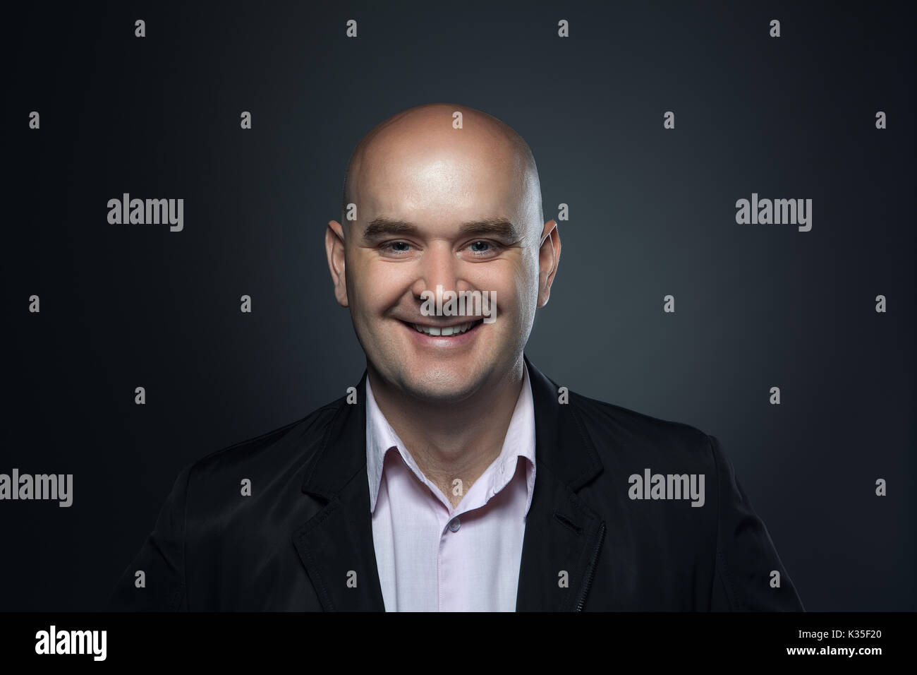 Portrait of a bald smiling, affable man in a suit against a dark background - Stock Image