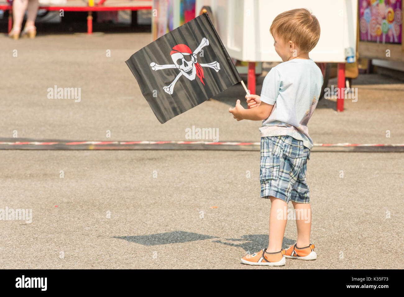 Portrait of a small boy holding a 'Skull and crossbones' flag. Stock Photo