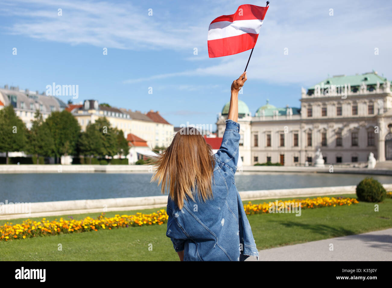 Young woman showing austrian flag in park outdoor - Stock Image