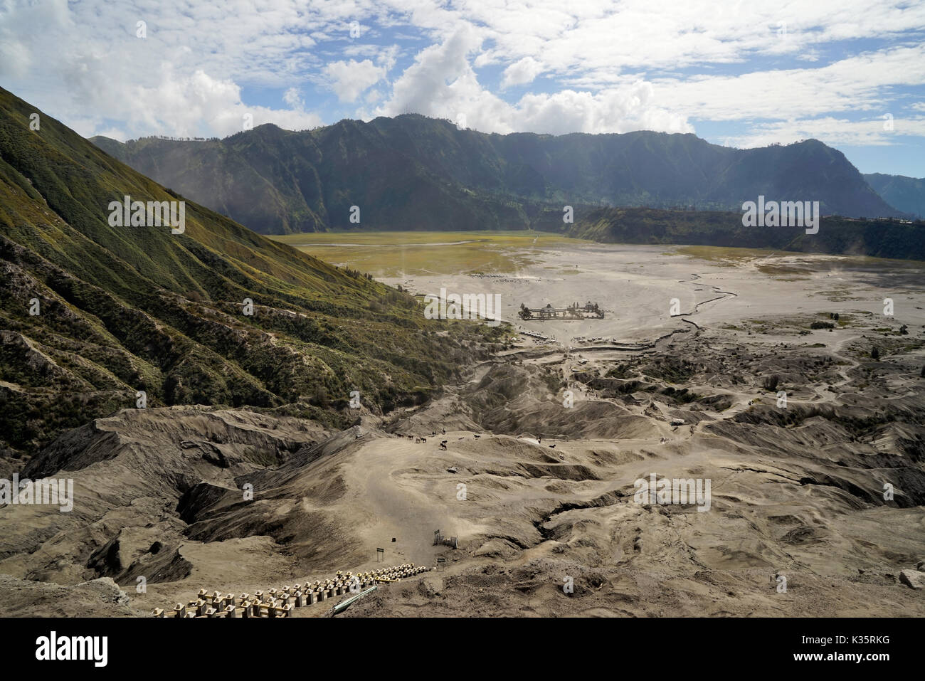 Panoramic view from  the top of the stairs heading towards the dusty valley with buddhist temple at the foot of mount Batok at the Tengger Semeru Nati - Stock Image