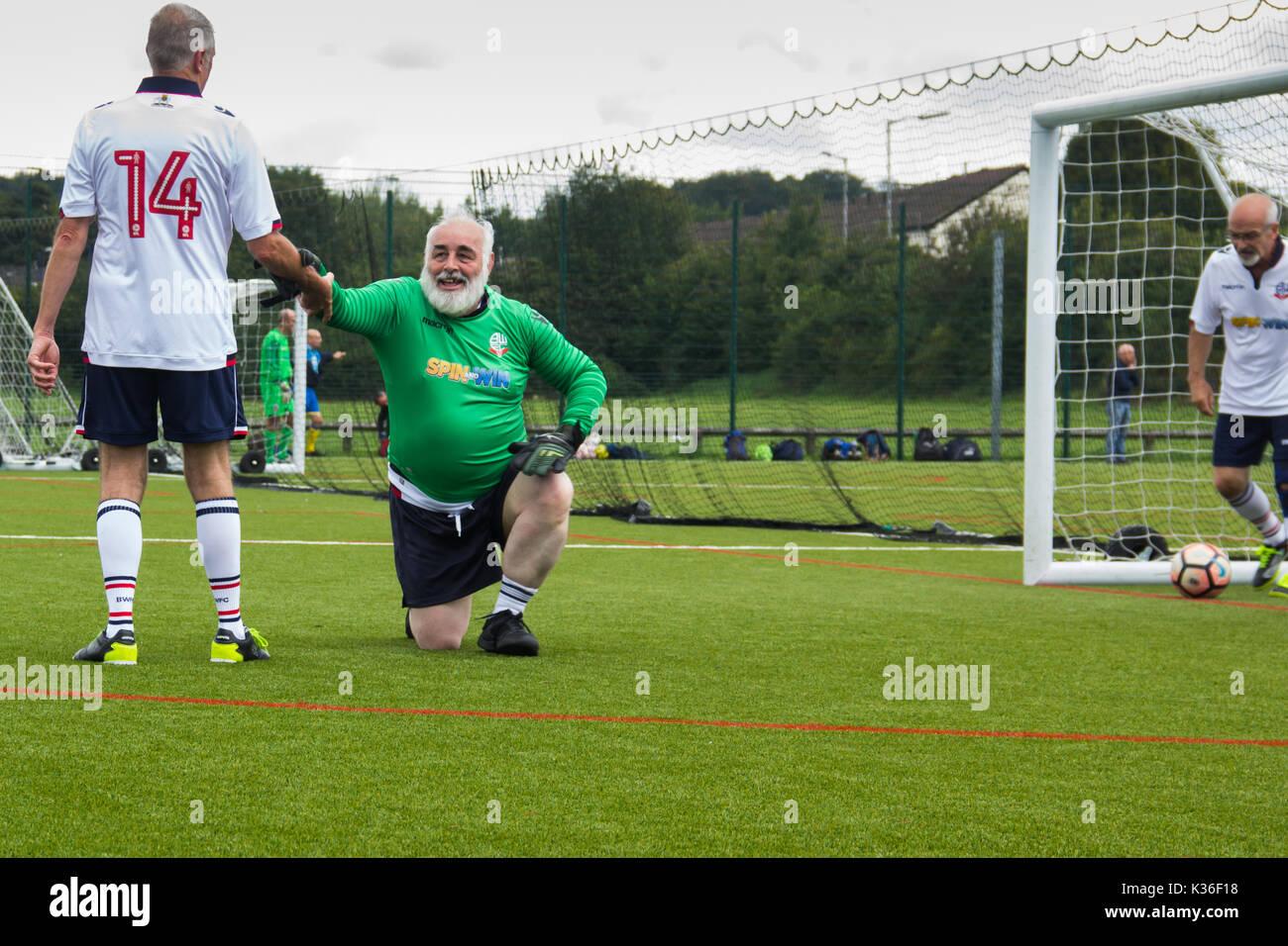 Heywood, Greater Manchester, UK. 1st September 2017. Today saw the kick-off of the second season for the Greater Manchester Over 60s Walking Football league at Heywood Sports Centre. The Bolton Wanderers B goalie receives a welcome helping hand to his feet as the defender fishes the fourth goal scored by Wakefield Wanderers out of the back of the net. Walking Football is one of the fastest growing areas of organised football in the UK, aimed at increasing health and fitness through physical activity in the over 50s, encouraged by football clubs, health professionals and Football Association. - Stock Image