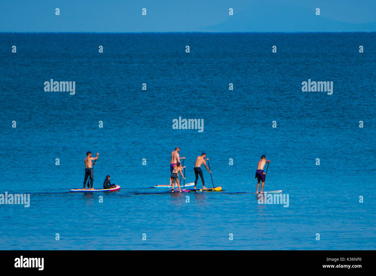 Aberystwyth Wales UK, Saturday 02 September 2017 UK Weather - On a bright sunny and warm September morning a group of friends go paddleboarding on the flat calm sea off Aberystwyth Wales. The weather is set to change overnight, turning overcast with a band of rain sweeping in from the west photo Credit: Keith Morris/Alamy Live News - Stock Image