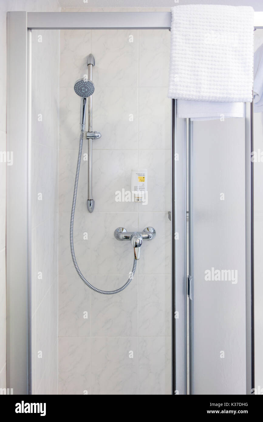 Typical hotel shower cubicle and towel - Stock Image