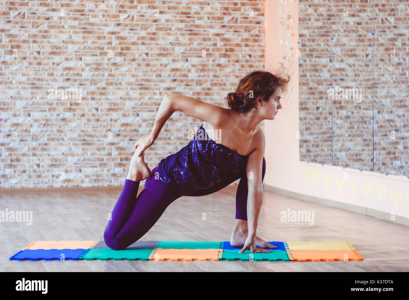 Full length side view portrait of beautiful young woman working out in luxury fitness center, doing yoga or pilates exercise without mat on wooden flo - Stock Image