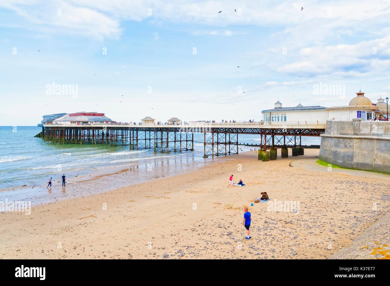 At low tide children play on the beach at the side of Cromer pier - Stock Image