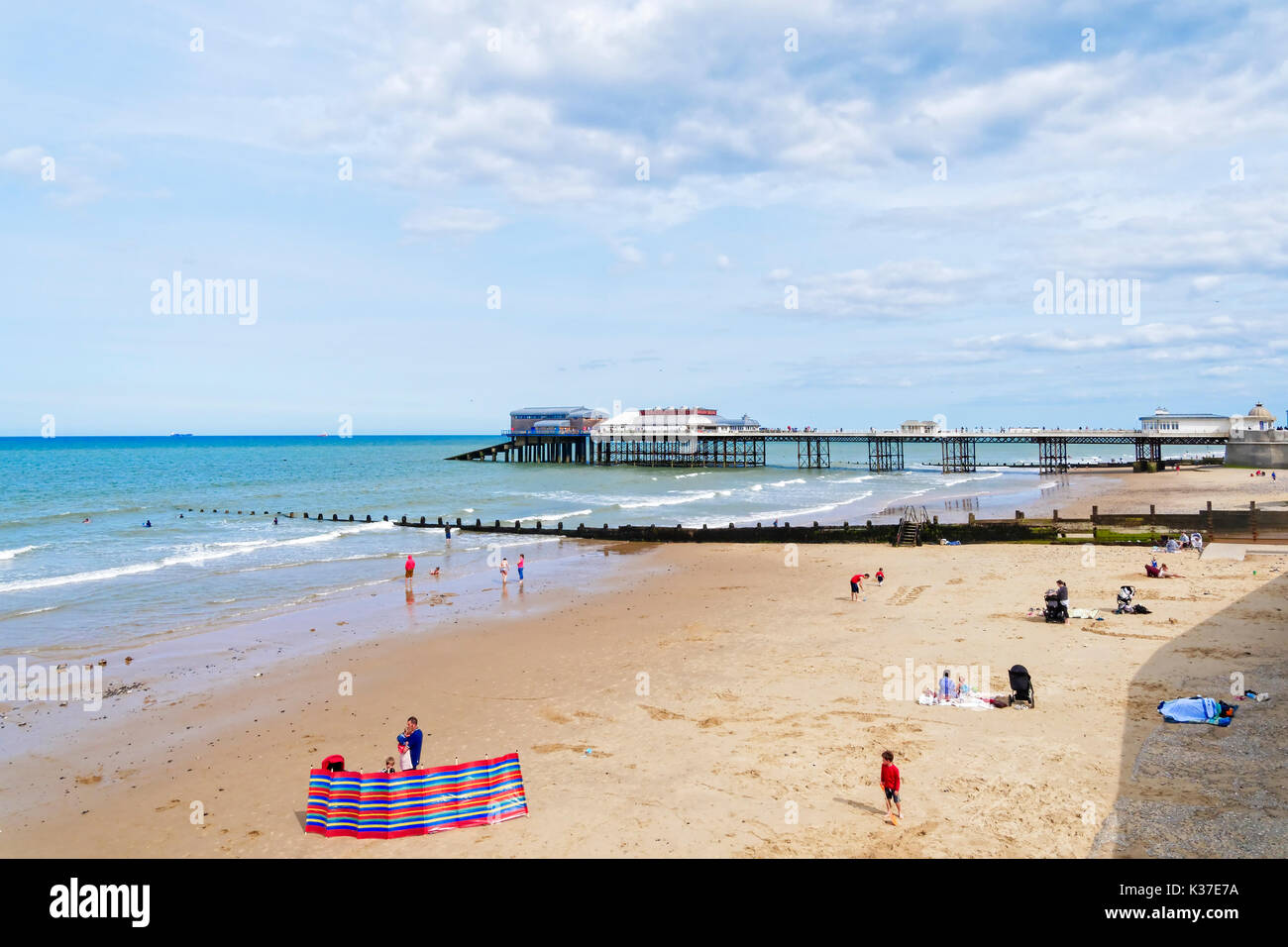 On a late summer afternoon people sit and play near the pier on Cromer beach - Stock Image
