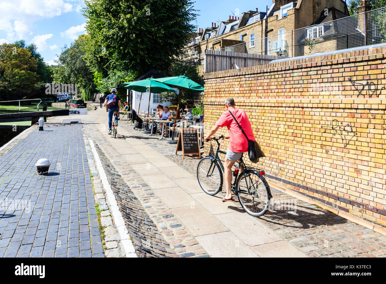 Two cyclists on the towpath of Regent's Canal, Islington, London, UK, people sitting outside at a canalside cafe - Stock Image
