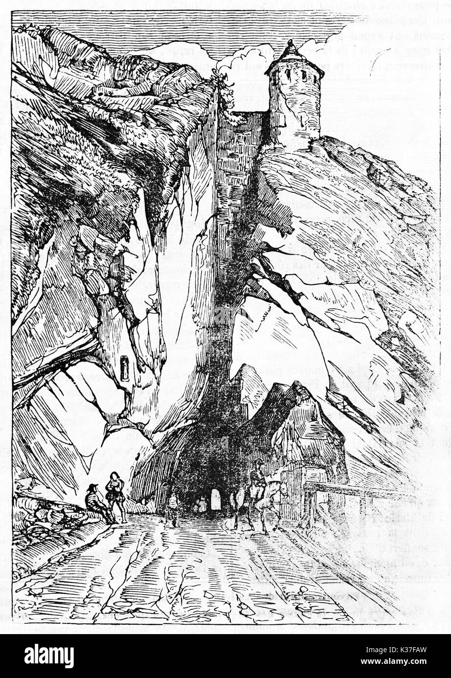 Ancient view of a rock crossed by a tunnel with a stone medieval tower on top. Porte Taillee in Besancon France. Created Old Illustration by Gigouc published on Magasin Pittoresque Paris 1834 - Stock Image