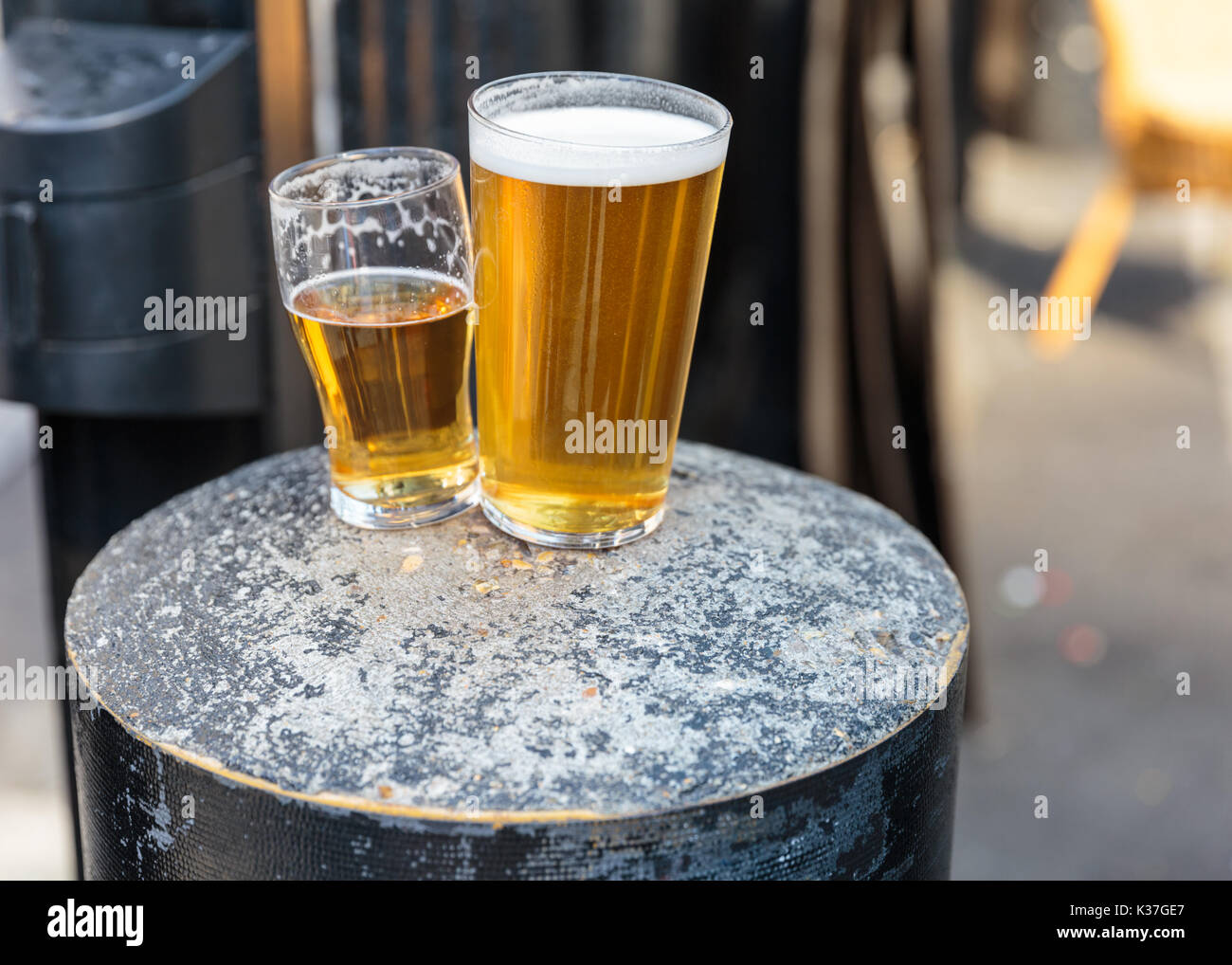 British pint and half pint of beer resting on a concrete stool, UK - Stock Image