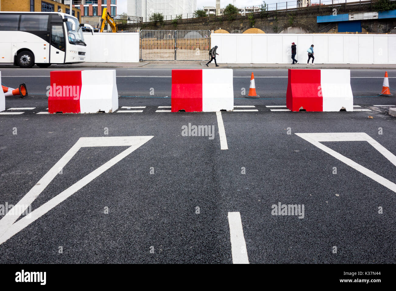 Red and white concrete blocks on a road junction blocking a street - Stock Image