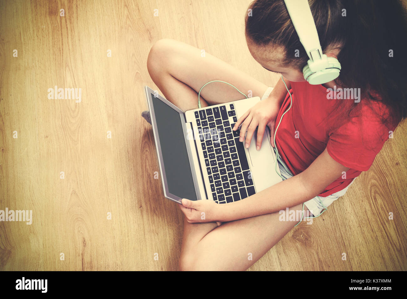 High angel view of a girl sitting on the floor and listening to music on her laptop (vintage effect). - Stock Image