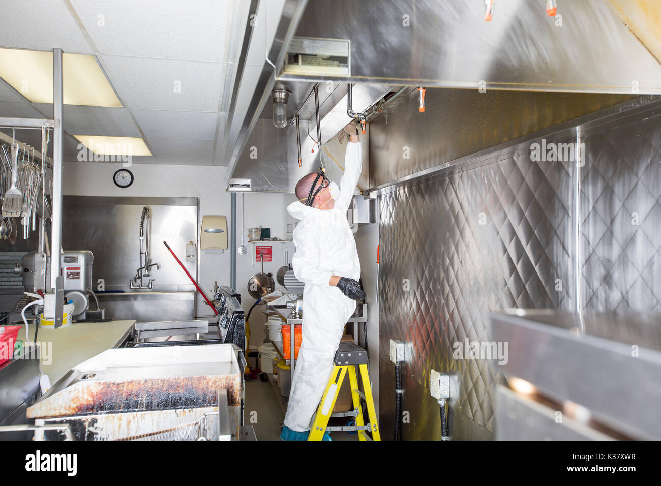 Commercial kitchen worker washing up at sink in professional kitchen - Stock Image