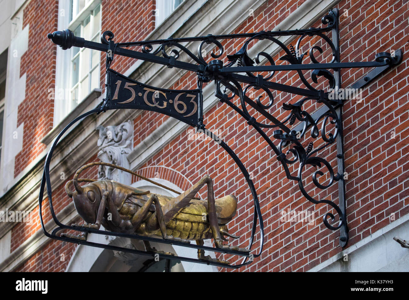 A Grasshopper sculpture hanging on Lombard Street in London, UK.  The Grasshopper is the representation of the family crest of Sir Thomas Gresham. - Stock Image