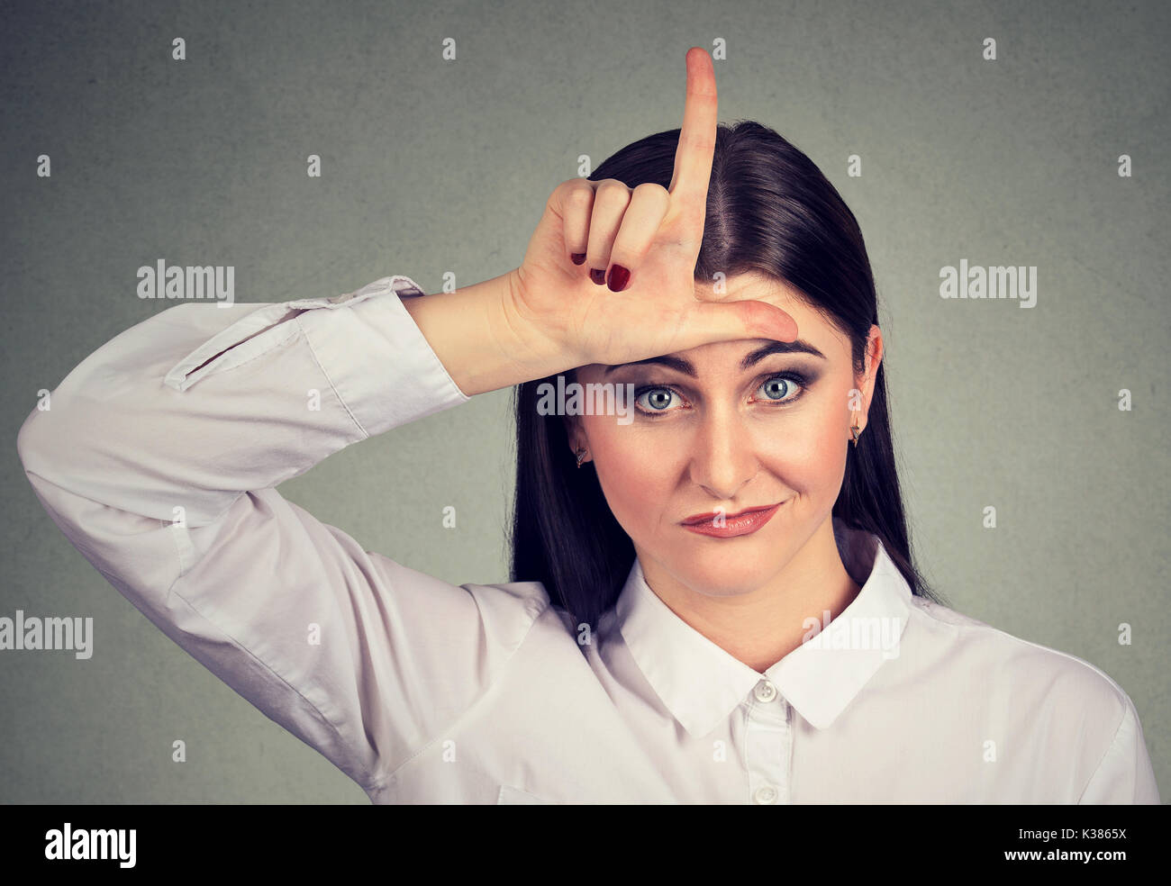 Angry woman showing loser sign looking at camera - Stock Image