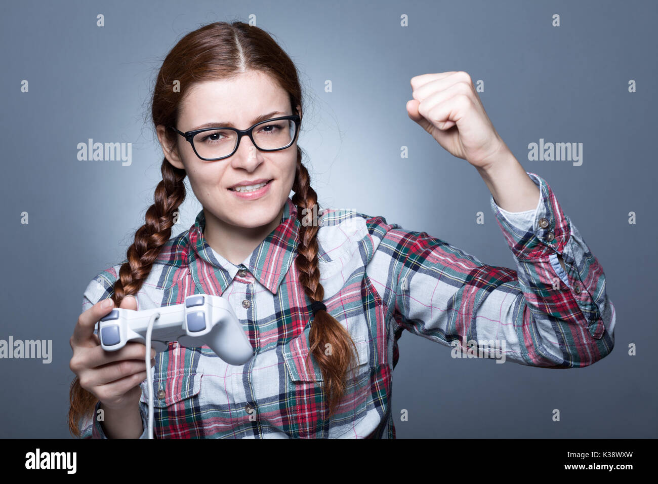Nerd Woman with Braid Playing Videogames with a Joypad - Stock Image