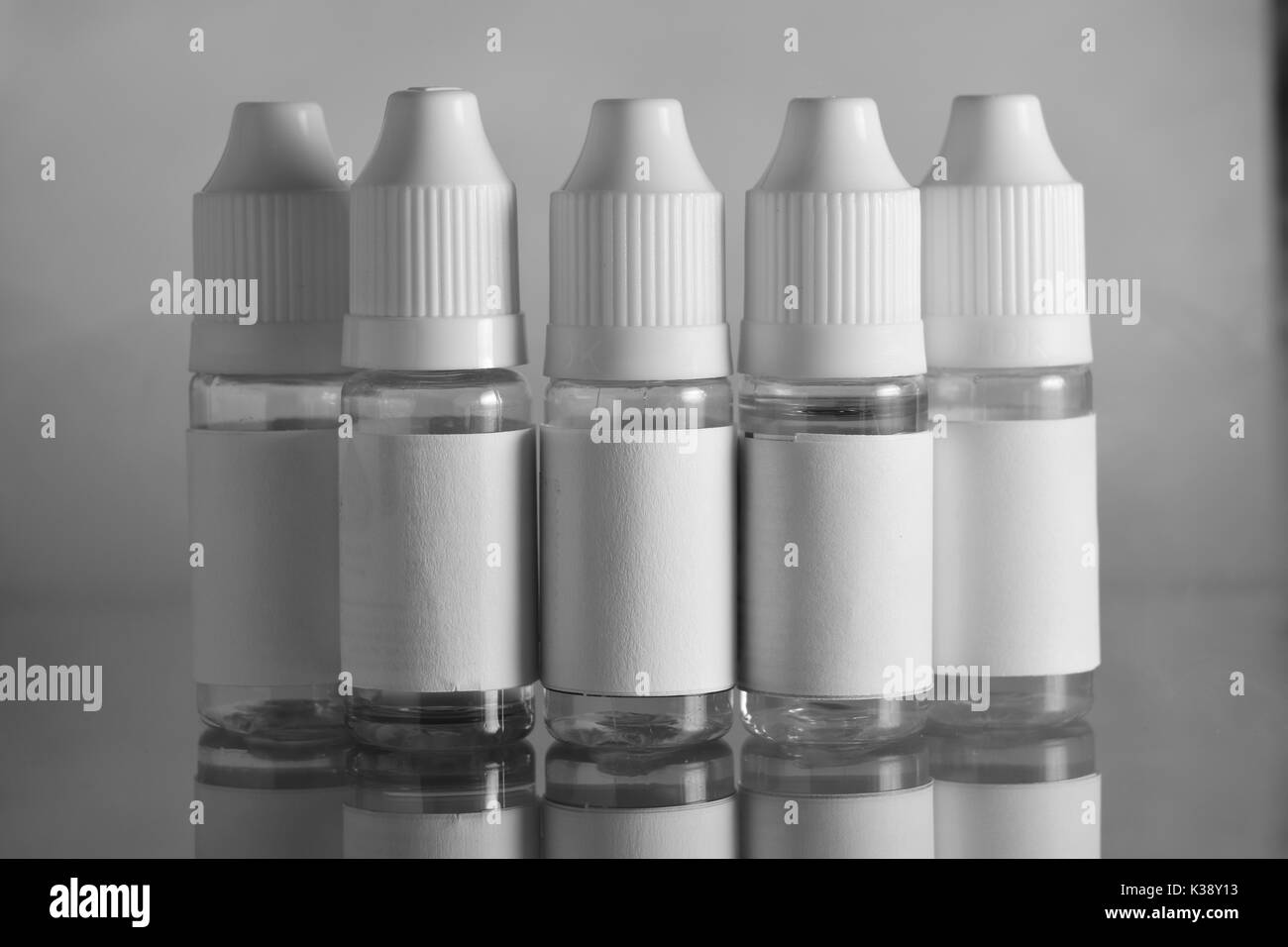 Isolated e liquid bottles for vaping devices, e cigarette, electronic cigarette, over a black background. Stock Photo