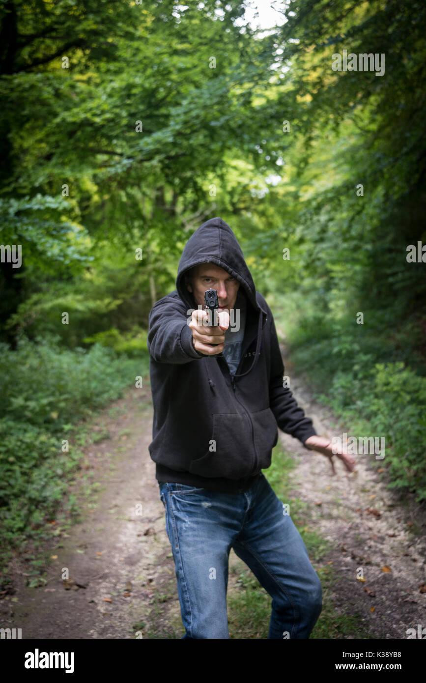 man pointing a gun wearing a hoodie - Stock Image