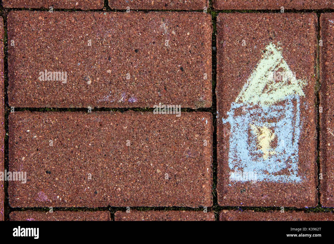Childish chalk drawing of a house on a brick pavement - Stock Image