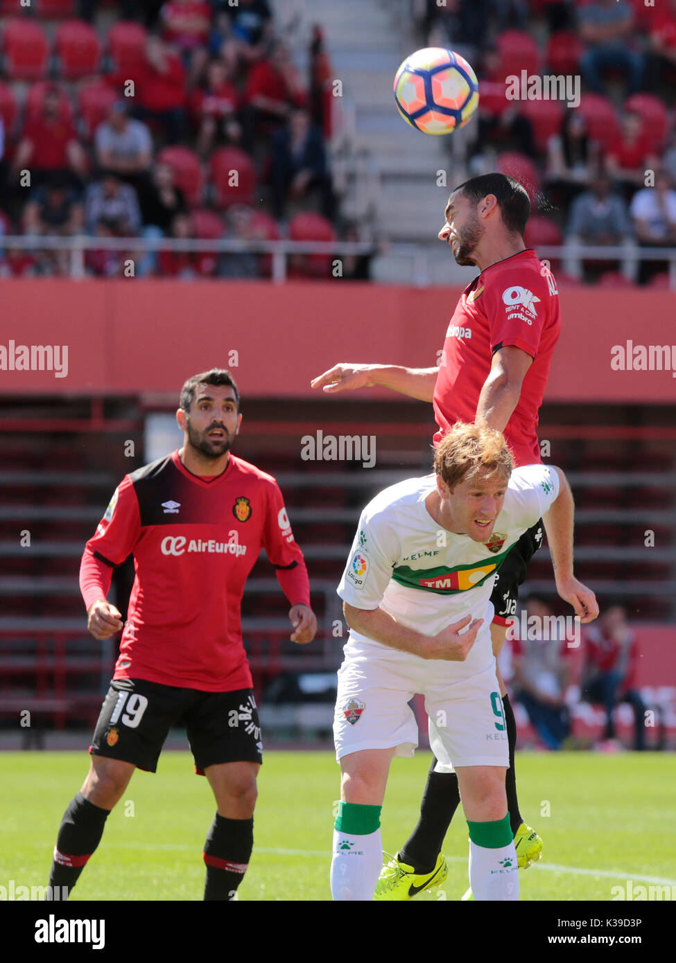 Real Mallorca player heads the ball against Sevilla atlético player during a match in Mallorca. - Stock Image