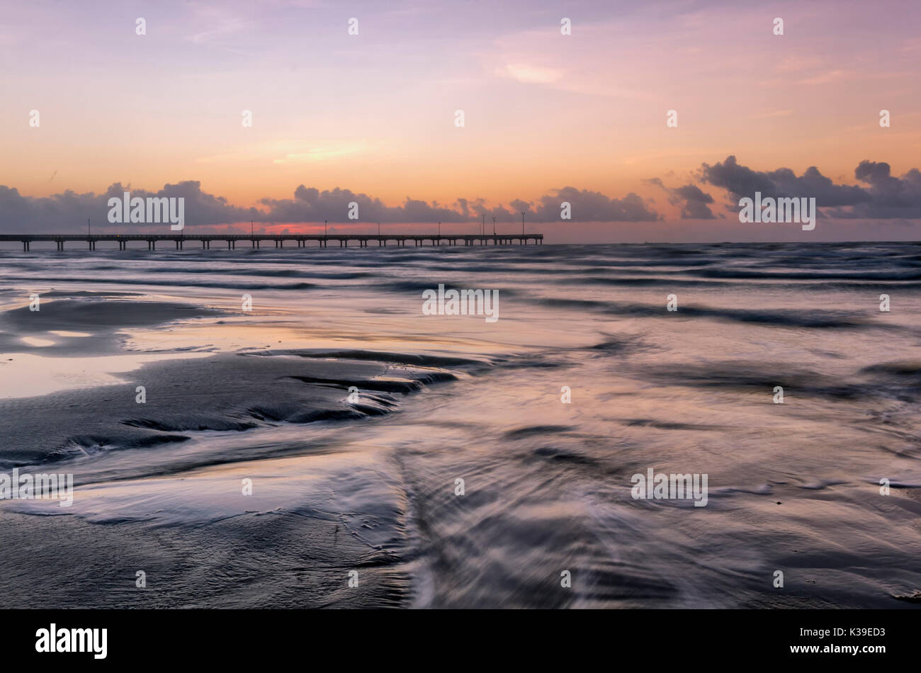 Horace Caldwell Fishing pier at sunrise with a long exposure on the crashing waves in the foreground located on Mustang Island in Port Aransas Texas - Stock Image