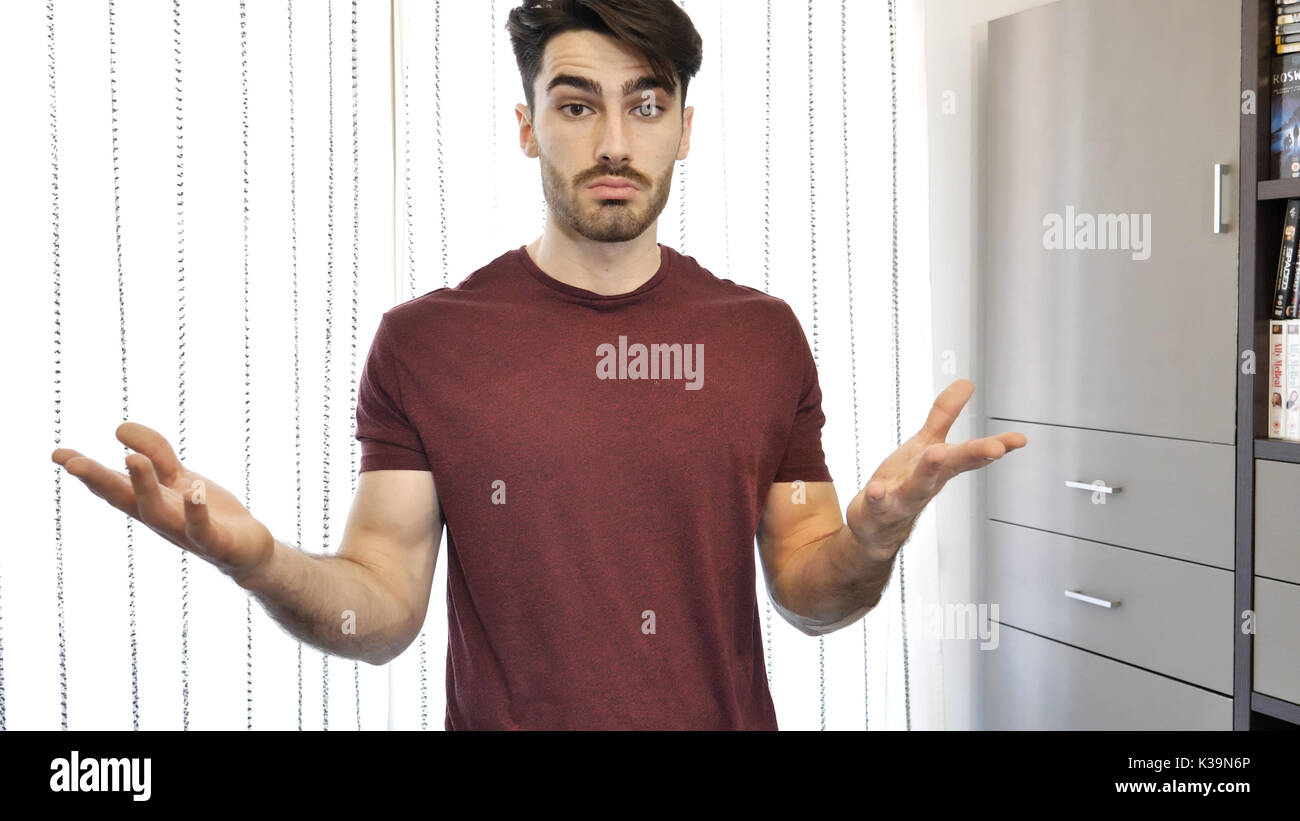 Confused or doubtful young man shrugging - Stock Image