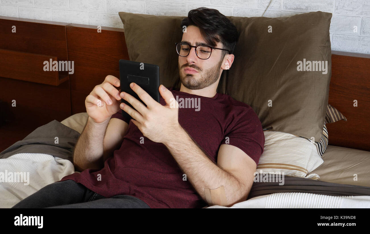 Young man on bed reading with ebook reader Stock Photo