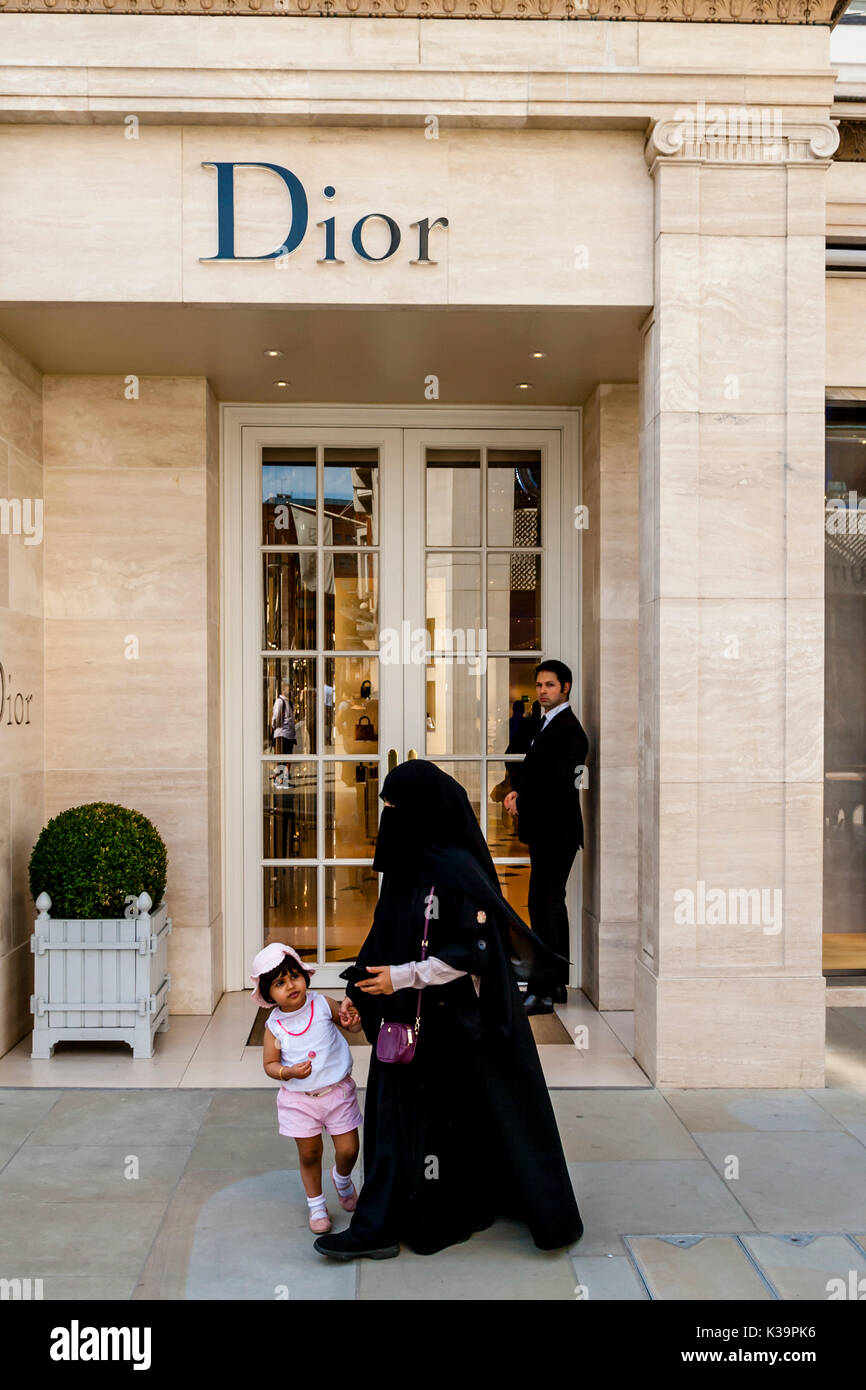 A Muslim Woman Wearing A Burka Walks Past The Dior Fashion Store In New Bond Street, London, UK - Stock Image