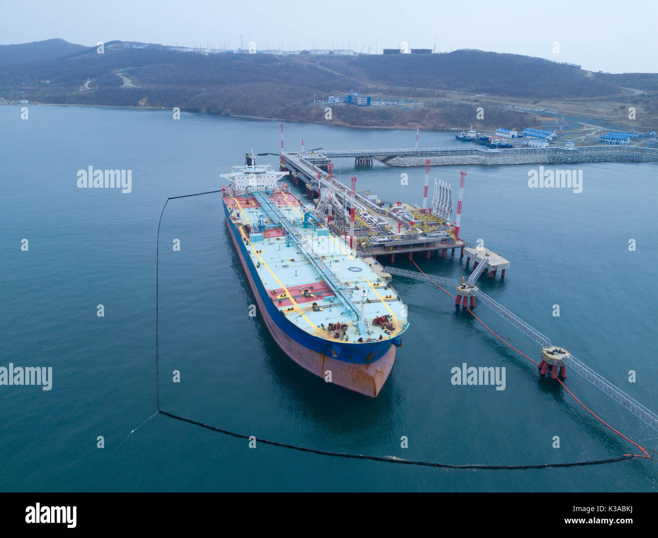 Liquid bulk oil tanker in port Fenced with booms - Stock Image