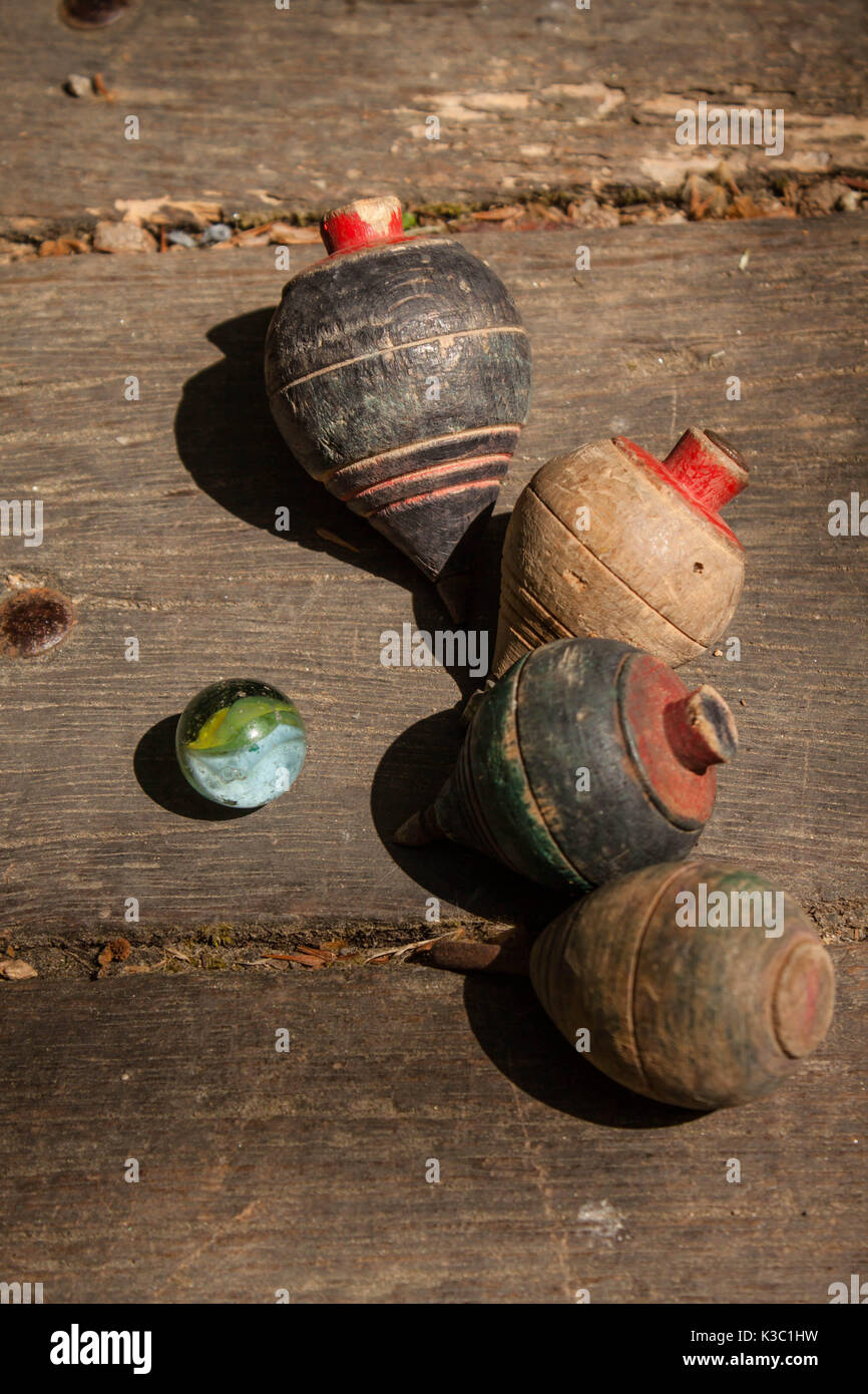 Old wooden spin toy top and marble on the wooden floor - Stock Image