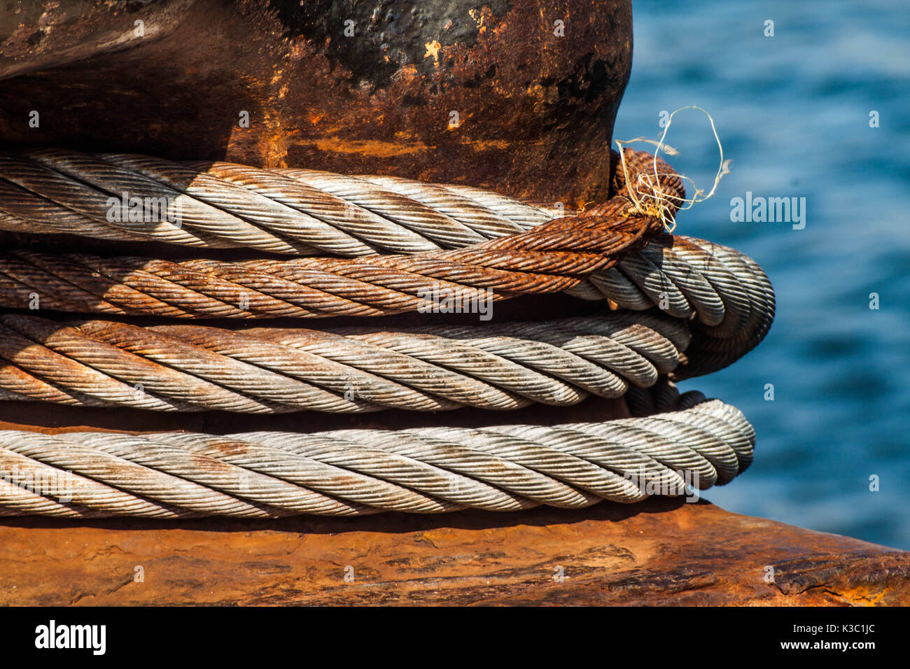 mooring bollard and cable at the harbour dock close up - Stock Image