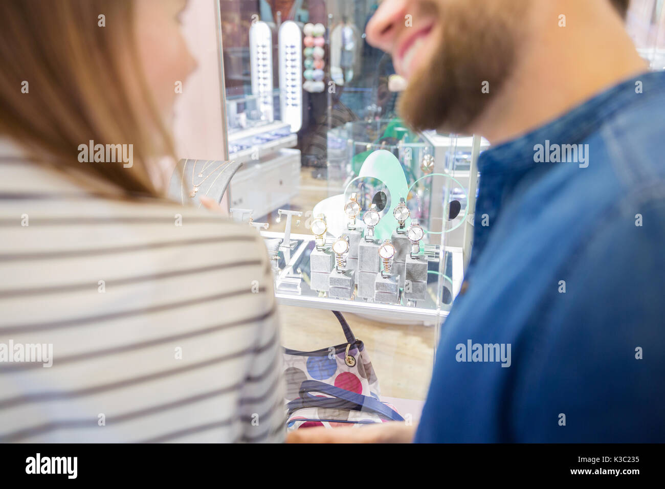 A photo of happy couple standing in front of jeweller's window. They're looking at the wristwatches. - Stock Image